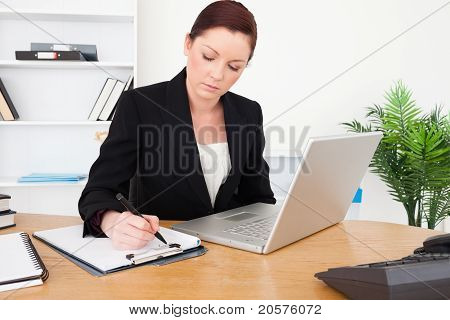 Young Beautiful Red-haired Female In Suit Typing On Her Laptop And Writing On A Notepad