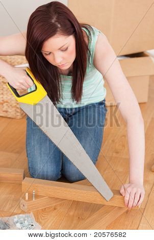 Attractive Red-haired Woman Using A Saw