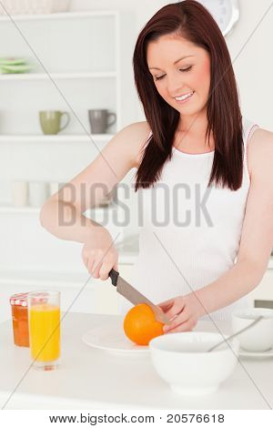 Young Attractive Red-haired Woman Cutting An Orange In The Kitchen