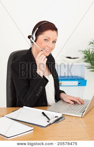 Young Good Looking Red-haired Woman In Suit Typing On Her Laptop And Using Headphones