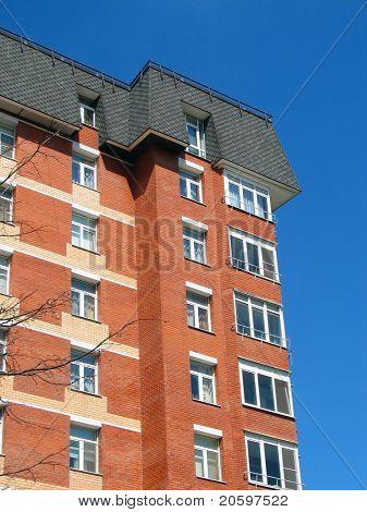 red-brick building offset against a deep blue sky