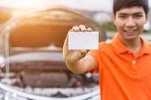 Aian Man Showing/holding Blank Of White Paper Or Business Card In Front Of Blur Damaged Car. For Car poster