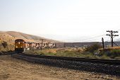 image of bnsf  - Diesel electric locomotives drag their train up Tehachapi Mountain California - JPG