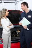 Handsome mechanic and client woman in auto repair shop.