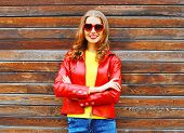 Fashion Autumn Smiling Woman Wearing A Red Leather Jacket On A Wooden Background poster