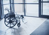 solitary wheelchair resting in the lobby of a hospital. Abstract healthcare and disability image poster