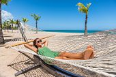 Happy girl relaxing on beach hammock in tropical vacation resort hotel. Holidays in the Caribbean ta poster