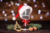 Christmas music concept. Microphone with hat and decoration on wooden table poster