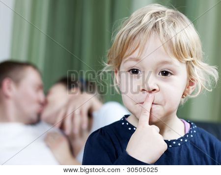 Blonde little girl making silence sign while mom and dad kissing in the background