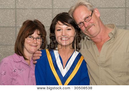 Young Woman In Graduation Gown With Family
