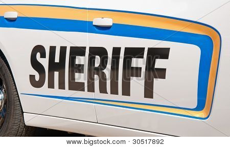 Sheriff texto en negro sobre el lado de una patrulla de blanca, con rayas de etiqueta amarilla y azul