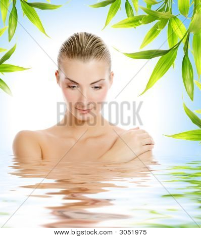 Young Beautiful Woman With Bamboo Frame Around Her Reflected In Water