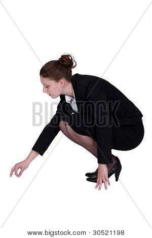 Businesswoman picking a speck up off the floor