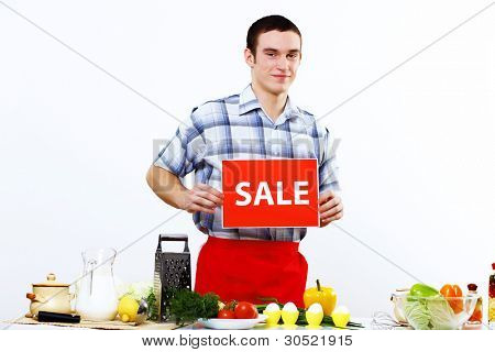Young man cooking fresh meal at home and holding sale sign
