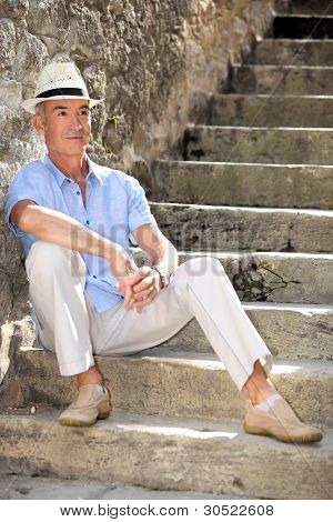 Middle-aged man sat on old stone steps