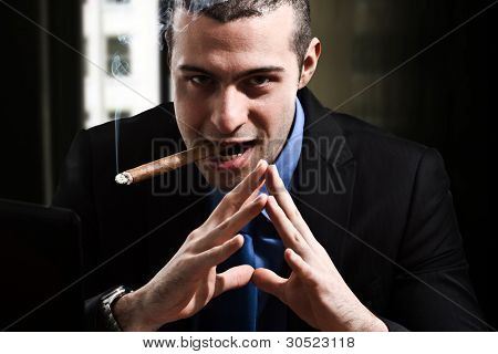 Shady man smoking a cigar in his office