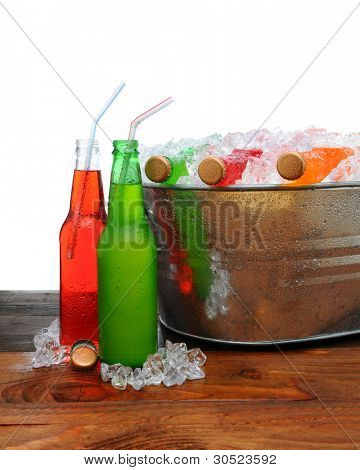 A metal party bucket on a wooden table full of cold soda pop. Two bottles on the table with drinking straws.