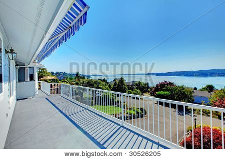 Front Door Porch With Water View And Grey House Exterior.