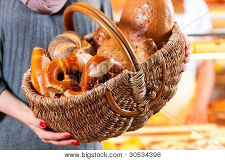 Female customer standing with breadbasket and fresh bread and rolls in bakery