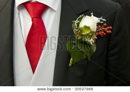 White rose in the buttonhole of the tail-coat of a groom, complementing the red necktie