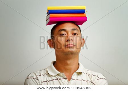 Ethnic Young Man With Books On Head