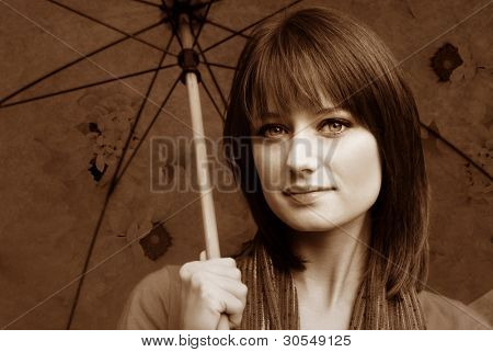 Sepia portrait of beautiful brunette with umbrella - blended with photos of flowers and texture for effect.