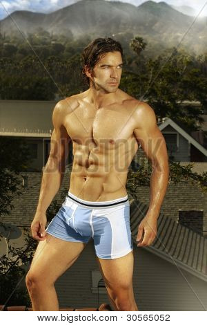 Outdoor portrait of a hunky male model turning in blue underwear with exotic location in the background