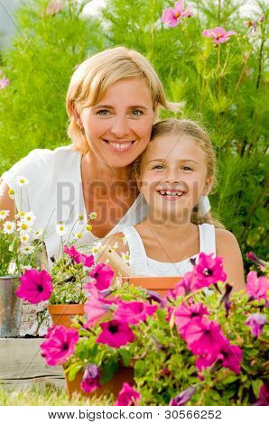 Gardening, planting concept - mother with daughter planting flowers into the flowerpot