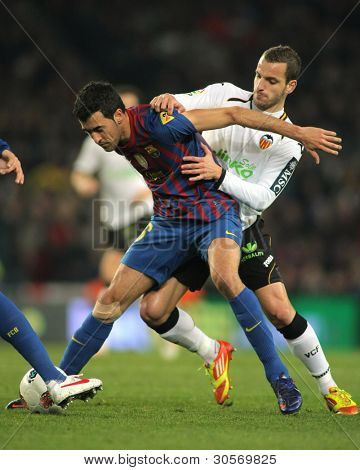 BARCELONA - FEB 19: Sergio Busquets(L) of FC Barcelona vies with Roberto Soldado(R) of Valencia CF during the Spanish league match at the Camp Nou stadium on February 19, 2012 in Barcelona, Spain