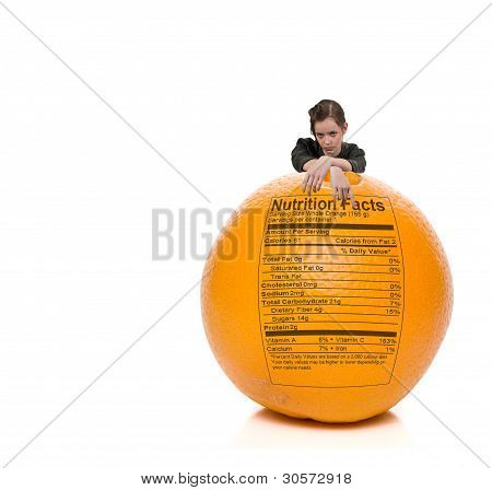 Teenage Woman Standing Behind Orange With Nutrition Label