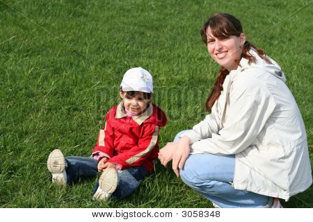 Little Girl With Her Mother In The Park Sitting On Green Grass
