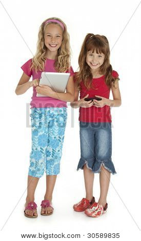 Two young girls standing,holding tablet device and smart phone on white background.