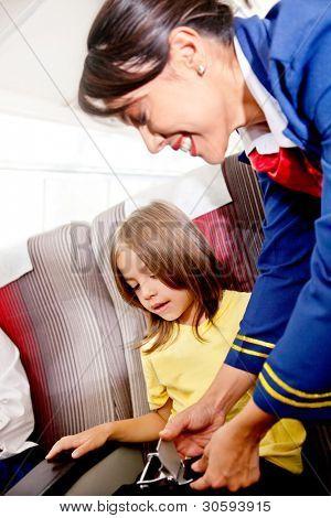 Aeromoça ajudando uma criança a prenda seu cinto de segurança