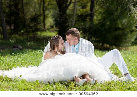 Bride and groom huggling sitting at green  grass