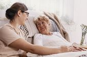 Elderly Woman In Hospital Bed With Social Worker Helping Her poster
