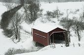 stock photo of covered bridge  - Winter landscape showing the red covered bridge on a country road snow is falling - JPG