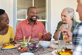 Happy smiling friends enjoying lunch together at home. Mature multiethnic people celebrating happy o poster