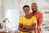 Smiling mature couple holding each other at home. Loving african couple standing in living room embr poster