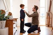 Single Father At Home Getting Son Wearing Uniform Ready For First Day Of School poster