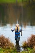 stock photo of fisherwomen  - beautiful blond girl fishing in pond at autumn - JPG