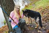 foto of fisherwomen  - girl with fihing rod and black dog at autumn - JPG