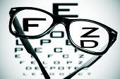 stock photo of snellen chart  - eyeglasses over a blurry eye chart - JPG