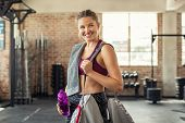 Young smiling woman in sportswear carrying gym bag. Happy fitness girl with sports bag after exercis poster