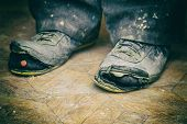 Old Torn Boots On The Mans Feet. Boots With Holes. Selective Focus poster