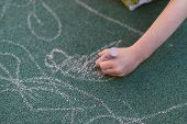 Child Draws With Chalk On The Street. Special Coating For Drawing On The Playground. The Kid Draws W poster
