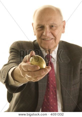 Senior Businessman Offering A Golden Egg