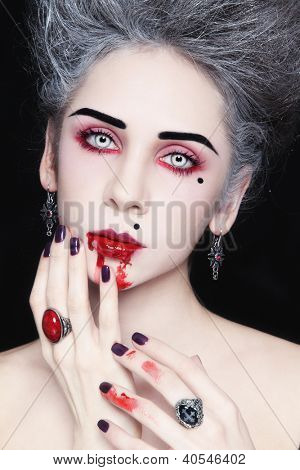 Portrait of young beautiful stylish gothic woman with vintage hairdo and bloody mouth