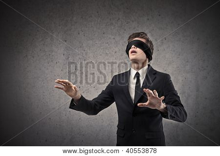 Young businessman walking blindfolded