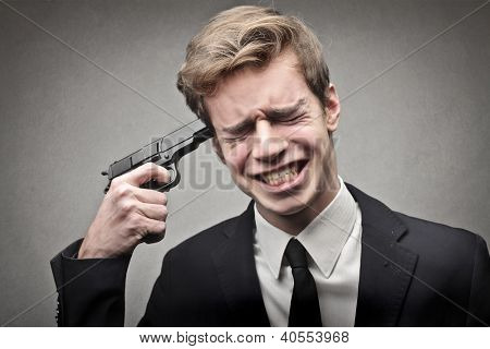 Young businessman pointing a gun to his head