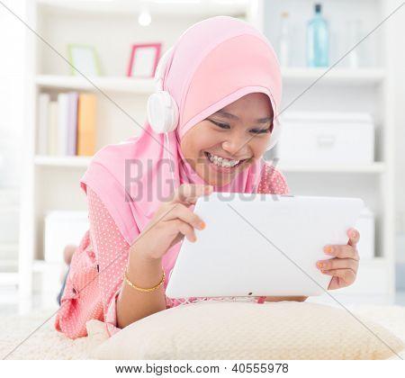 Southeast Asian teenager listen mp3 headphone at home. Muslim teen girl living lifestyle.